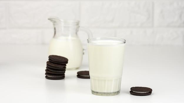 Copo de leite cheio, ao lado de uma pilha de biscoitos redondos com gotas de chocolate em uma mesa branca