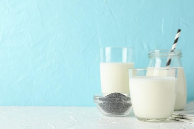 Copo de leite chia e sementes de chia na mesa azul. fechar-se