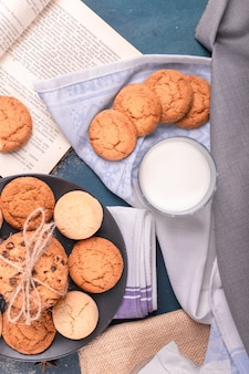 Copo de leite com biscoitos e livro