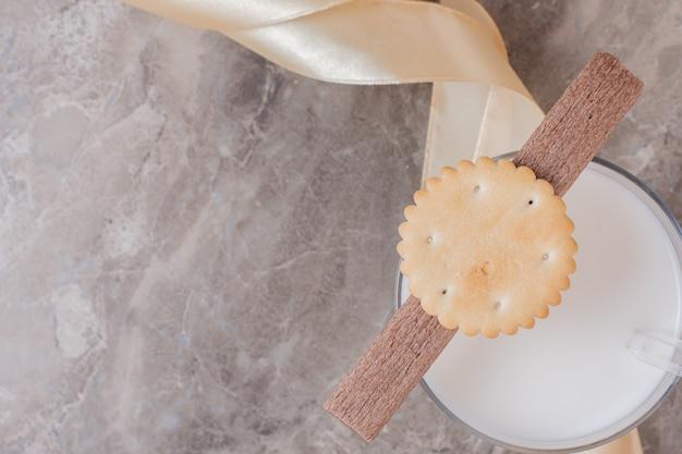 Copo de leite com biscoitos na mesa de mármore.