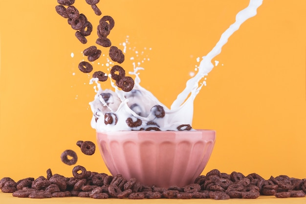 Copo de leite com cereais de chocolate caindo e respingos de leite.