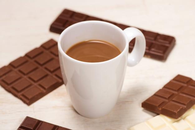 Copo de leite com chocolate e chocolates em barra na mesa