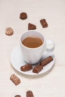 Copo de leite com chocolate e vários chocolates na mesa