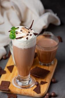 Copo de leite com chocolate na superfície escura.