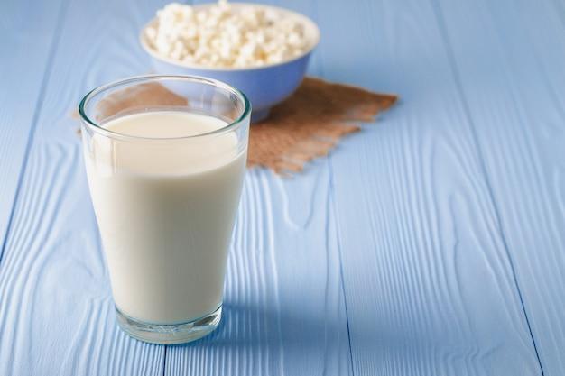 Copo de leite com tigela de queijo cottage na madeira azul