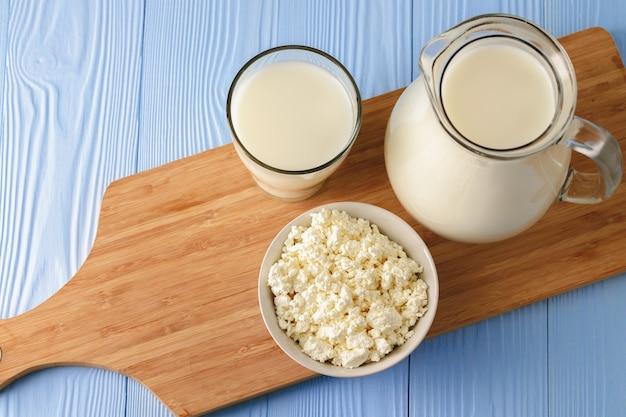 Copo de leite com tigela de queijo cottage no fundo azul de madeira