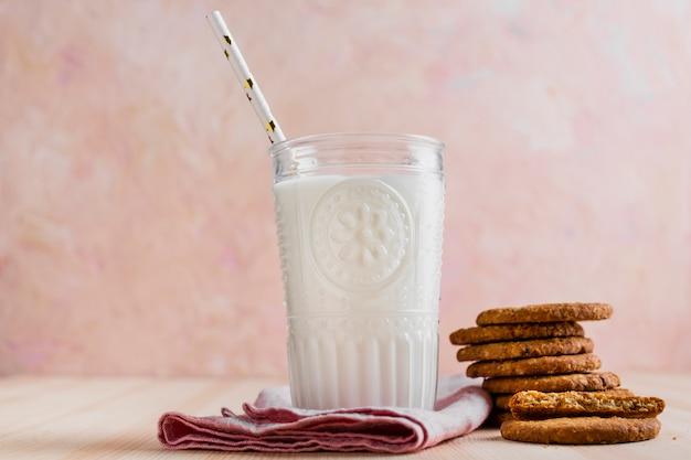 Copo de leite com vista frontal com palha e biscoitos