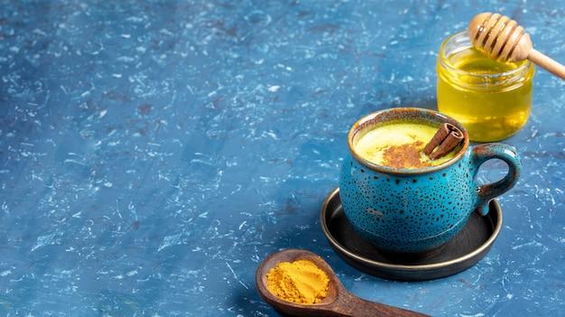 Copo de leite de açafrão dourado, colher de pau com curcuma em pó e pote de mel no azul. foco seletivo. copie o espaço.