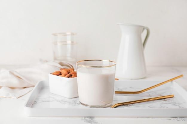 Copo de leite de amêndoa saboroso e tigela com nozes em fundo claro