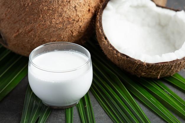 Copo de leite de coco colocado em fundo escuro