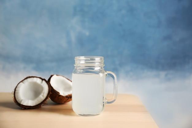 Copo de leite de coco e nozes na mesa de madeira