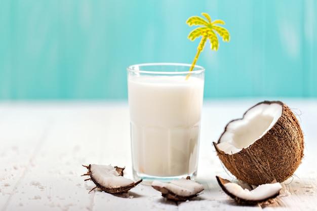 Copo de leite de coco na mesa de madeira branca. foco seletivo