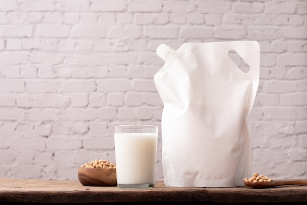 Copo de leite de soja e saco de armazenamento de leite na mesa de madeira.