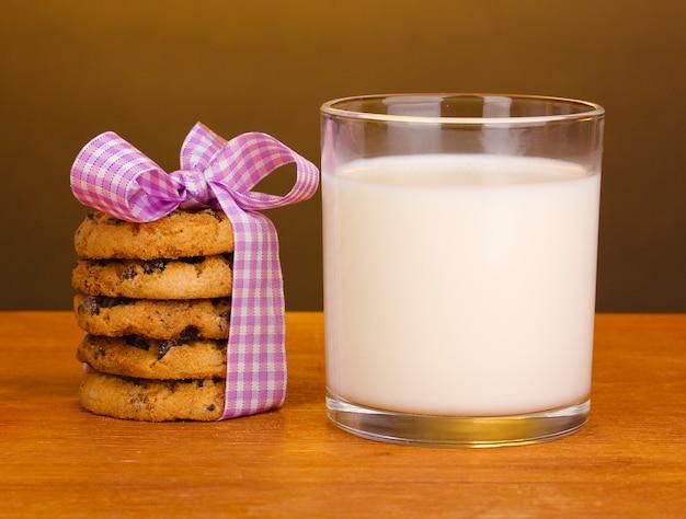 Copo de leite e biscoitos na mesa de madeira na superfície marrom