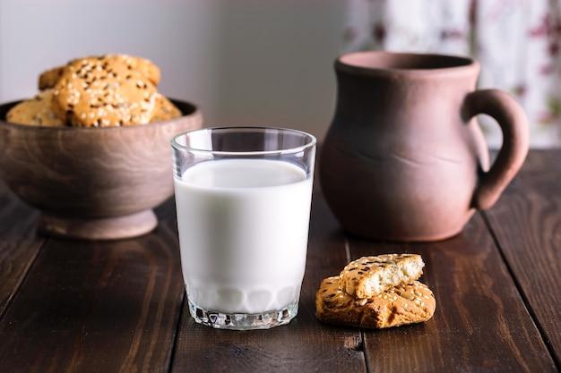 Copo de leite e biscoitos na mesa de madeira