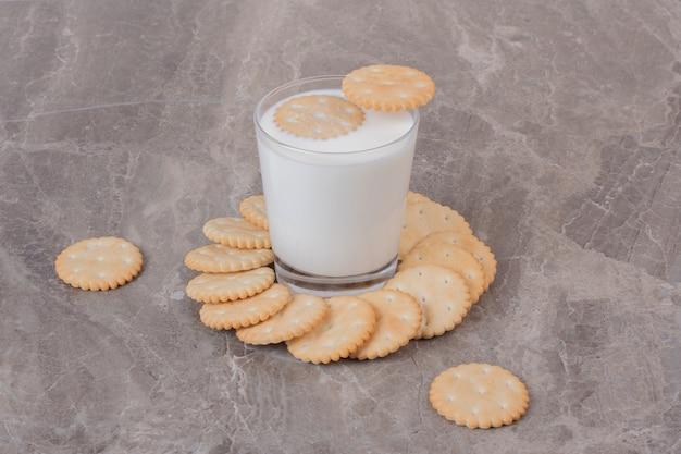 Copo de leite e biscoitos redondos na superfície de mármore.