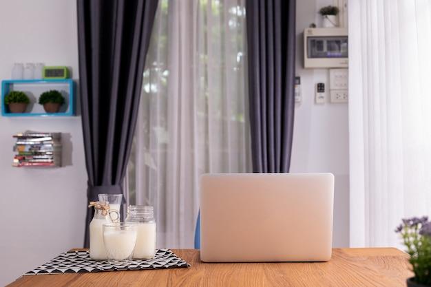 Copo de leite e laptop na sala de estar.