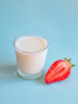Copo de leite e morangos maduros em uma superfície azul