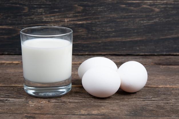 Copo de leite e ovos de galinha em uma mesa de madeira