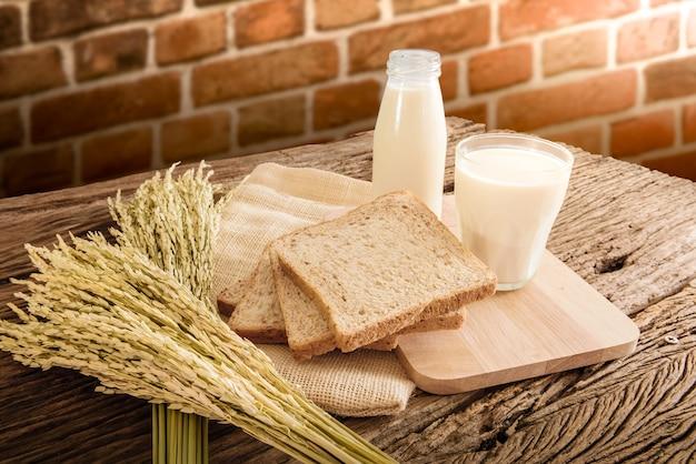 Copo de leite e pão integral na placa de madeira. cor do estilo retro