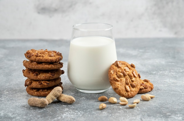 Copo de leite e pilha de biscoitos com mel na mesa de mármore.