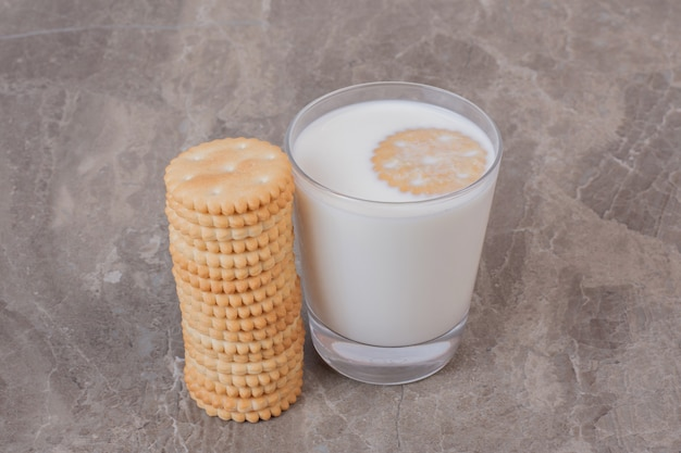 Copo de leite e pilha de biscoitos mesa de mármore.