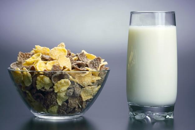 Copo de leite e um prato de flocos de milho. comida natural crua