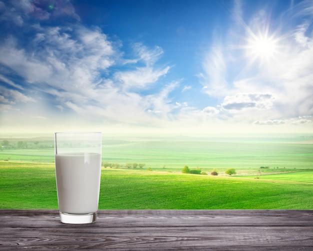 Copo de leite fresco contra pastagem verde ondulada