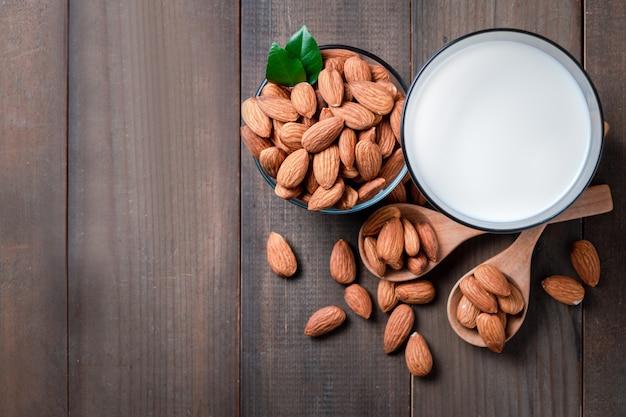 Copo de leite fresco e amêndoas nozes na mesa de madeira, as amêndoas são nozes muito populares e com alto teor de proteínas. comida saudável.