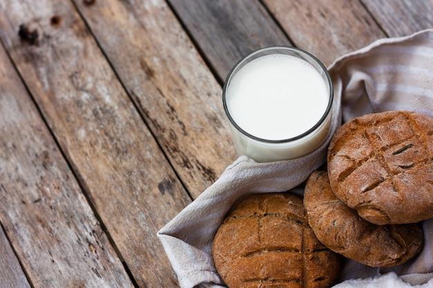 Copo de leite fresco e pão achatado de centeio marrom redondo sobre uma mesa de madeira rústica.