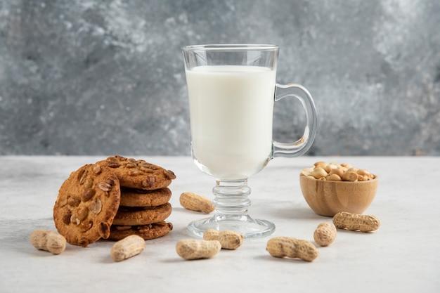 Copo de leite fresco e saborosos biscoitos com amendoim na mesa de mármore.