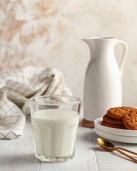 Copo de leite, jarro, biscoitos. o conceito de produtos lácteos, o uso de leite,