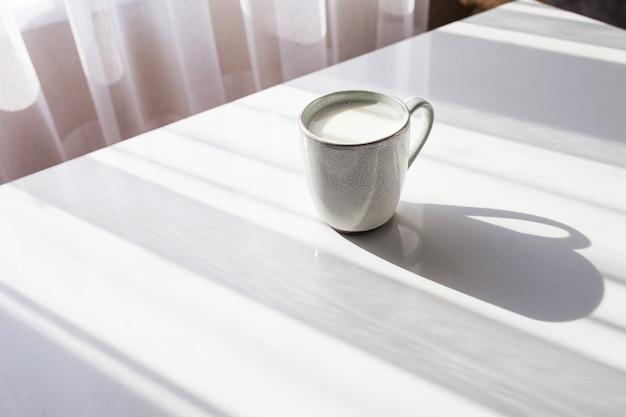 Copo de leite na mesa branca. café da manhã ou almoço saudável. luz do sol e sombra.