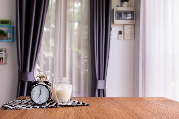 Copo de leite na mesa de madeira na sala de estar.