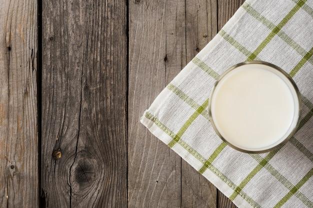 Copo de leite no guardanapo xadrez sobre a mesa de madeira