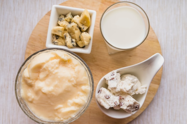 Copo de leite perto de placas com conjunto de queijo saboroso