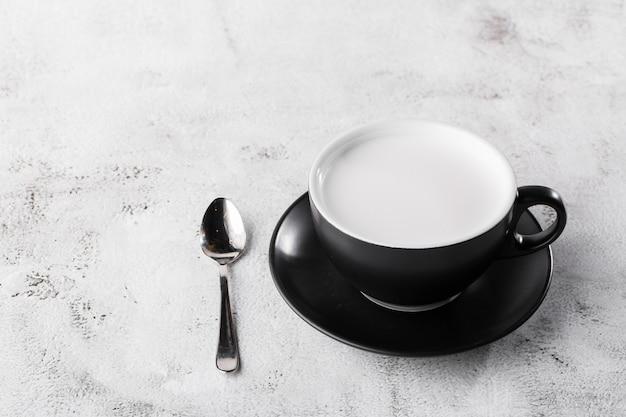 Copo de leite quente no copo escuro, isolado no fundo de mármore brilhante. visão aérea, copie o espaço. publicidade para o menu de café. menu de café. foto horizontal. bebidas tradicionais para o inverno