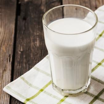 Copo de leite saudável no guardanapo branco sobre a mesa de madeira