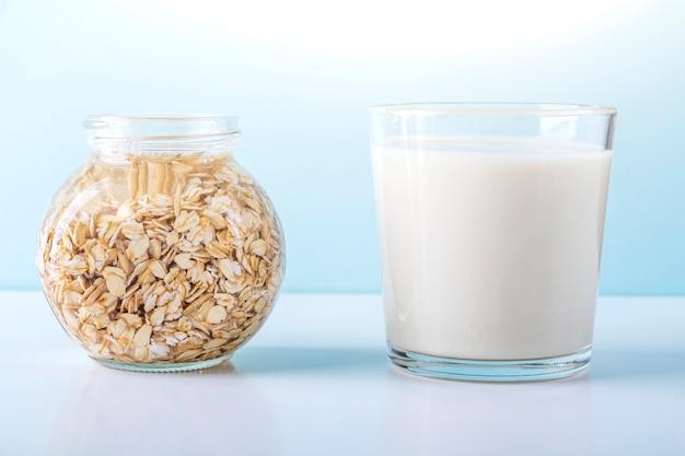 Copo de leite vegetal de aveia e frasco com farinha de aveia de imersão. conceito de fazer leite vegetal orgânico à base de vegetais, sem lactose.