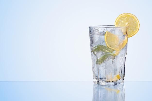 Copo de limão bebe com limões frescos, hortelã e cubos de gelo no azul.