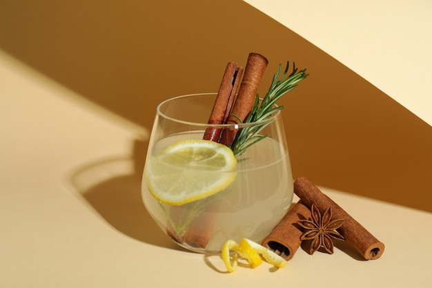 Copo de limonada com canela e alecrim em fundo bege