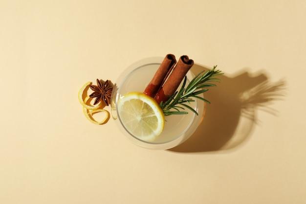 Copo de limonada com canela e alecrim na superfície bege