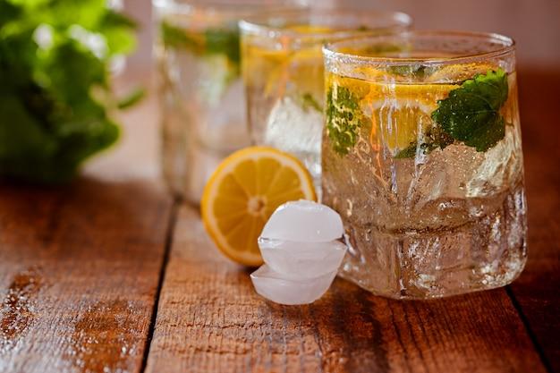 Copo de limonada com limão e hortelã no fundo de madeira