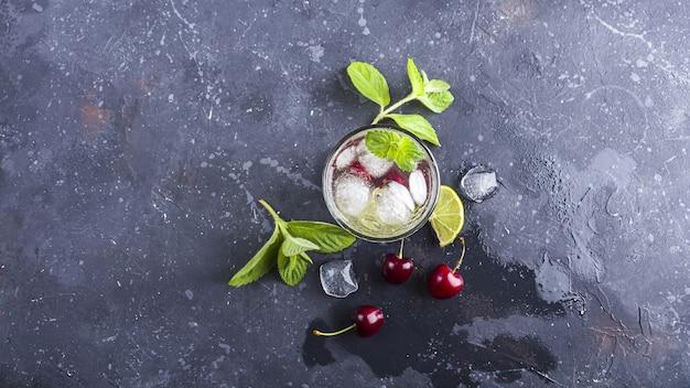 Copo de limonada de verão ou chá gelado. bebida refrescante de desintoxicação com cereja e hortelã em fundo escuro.