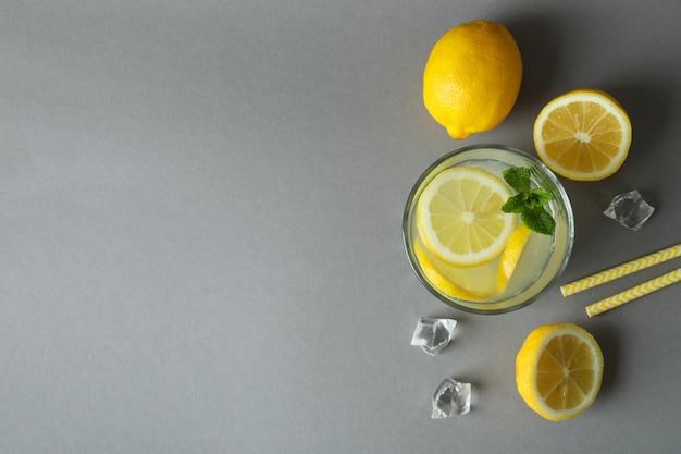 Copo de limonada e ingredientes em fundo cinza claro