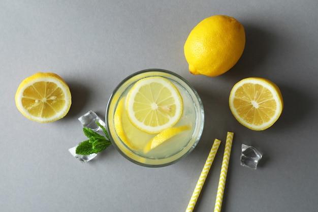 Copo de limonada e ingredientes em superfície cinza claro