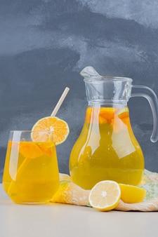 Copo de limonadas com rodelas de limão na parede azul.
