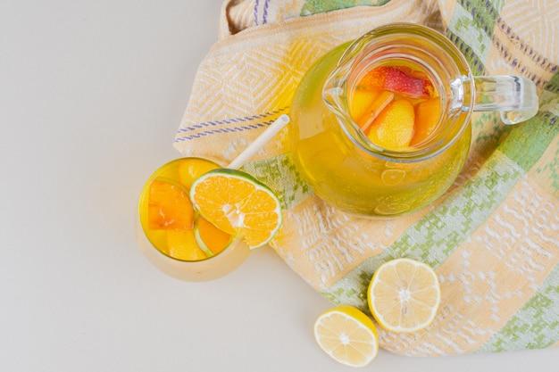 Copo de limonadas com rodelas de limão na superfície branca.