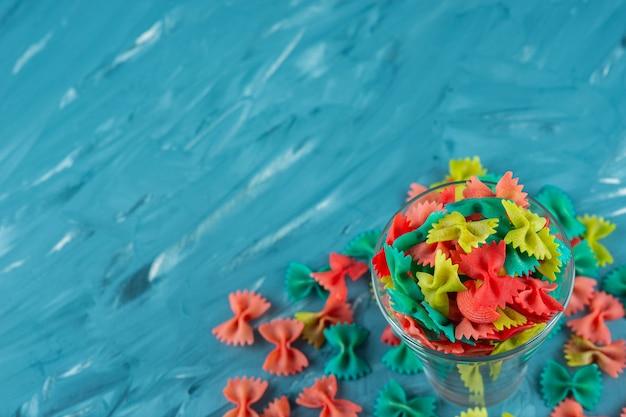 Copo de macarrão farfalle cru colorido sobre fundo azul.