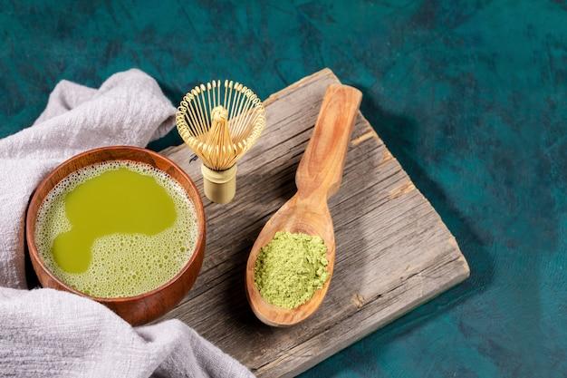 Copo de madeira do chá verde do matcha, pó do matcha na colher de madeira, batedor de bambu na placa de madeira velha no fundo esmeralda.